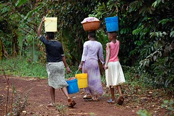 image of older girls carrying water
